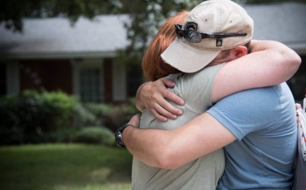 Man and woman hug in front of home
